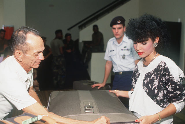 William W. Giavelli, a military customs agent, checks the luggage of Sergeant William C. Rinaman of the 24th Security Police Squadron, and of Rinaman's wife Aydee, as they leave Panama after President Bush's order to reduce the number of US citizens in the country