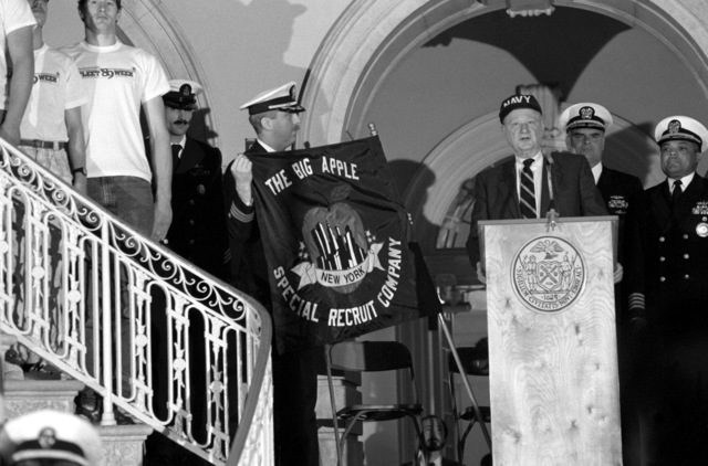 Mayor Ed Koch speaks during the swearing-in ceremony for the Big Apple Special Recruit Company. Standing behind Koch is Vice Admiral Roger F. Bacon, Commander, Submarine Force, US Atlantic Fleet, who administered the oath of enlistment to the members of the company