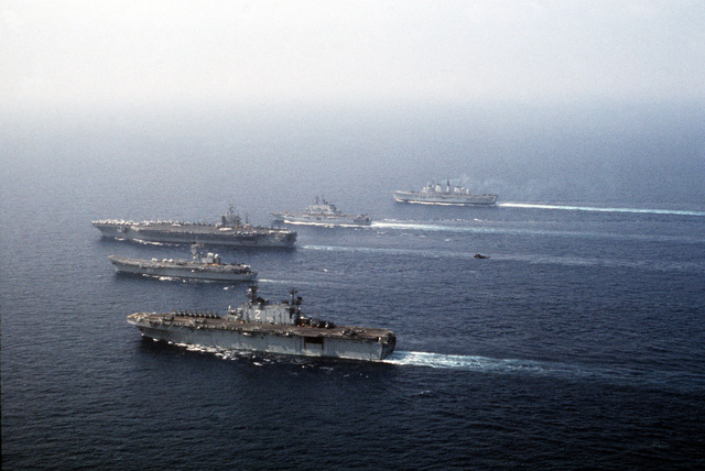 Ships from four nations sail in formation during the NATO Southern Region exercise DRAGON HAMMER '90. The ships are, from front: amphibious assault ship USS SAIPAN (LHA 2), the Spanish aircraft carrier SPS PRINCIPE DE ASTURIAS (R-11), the nuclear-powered aircraft carrier USS DWIGHT D. EISENHOWER (CVN 69), the Italian light aircraft carrier ITS GIUSEPPE GARIBALDI (C-551), and the British light aircraft carrier HMS INVINCIBLE (R-05)