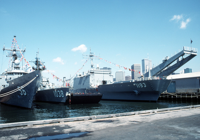 A starboard bow view of, from left: the guided missile frigate USS SIMPSON (FFG-56), the frigate USS MCCLOY (FF-1038), and the tank landing ship USS FAIRFAX COUNTY (LST-1193) moored at the pier in Brooklyn during Fleet Week