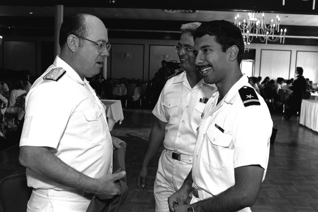 Rear Adm. Benjamin Montoya, commander, Naval Facilities Engineering Command, a Class of '58 graduate of the U.S. Naval Academy, speaks with ENSIGN Arturo Martinez, an '87 graduate, as CAPT. Joe Mancias Jr. looks on during the Ninth Annual Hispanic Officers Recruiting Conference