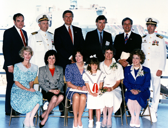 At the christening and launch of the dock landing ship USS RUSHMORE (LSD 47): seated, left to right, Mrs. P.D. Hurst; Mrs. A.L. Bossier; Meredeth Brokaw, ship's sponsor; Kimberly Graff, flower girl; Linda Mickelson, matron of honor; and Rep. Lindy Boggs, D-LA. Standing, left to right: A.L. Bossier, CEO, Avondale Industries, Inc.; Captain J.F. King, NAVSEA: Governor G.S. Mickelson of South Dakota; Senator, Larry Pressler, R-SD; Tom Brokaw, NBC News; and Captain P.D. Hurst, SUPSHIP, New Orleans