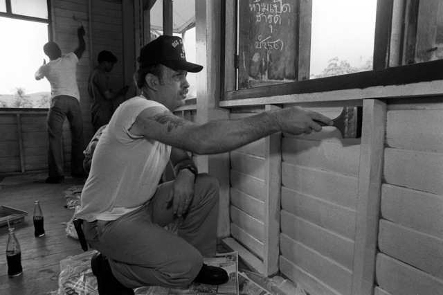 A crewman from the guided missile cruiser USS GRIDLEY (CG-21) helps to paint a schoolhouse as part of a community relations project. Crewmen from both the GRIDLEY and the destroyer USS JOHN YOUNG (DD-973) are taking part in the project during Liberty in Phuket