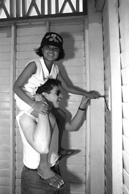 Radioman 2nd Class William Patterson, a crewman aboard the destroyer USS JOHN YOUNG (DD-973), holds a local child on his shoulders as she helps him paint a schoolhouse wall. Crewmen from both the GRIDLEY and the destroyer USS JOHN YOUNG (DD-973) are taking part in the project during Liberty in Phuket