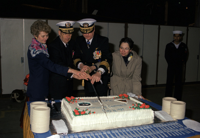 Rear Admiral (RADM) (lower half) Thomas F. Hall, incoming commander, Iceland Defense Force (IDF), second from left, and RADM Eric A. McVadon Jr., outgoing commander, IDF, join with two guests to make the first slice in a cake following the IDF change of command ceremony
