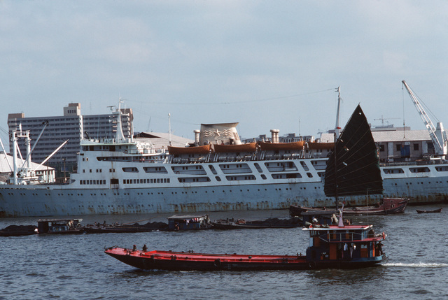 A barge, coal scows, and a junk pass an ocean liner