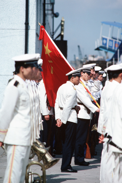 A flag bearer adjusts his cap as he and other members of a Chinese navy band wait on the pier for their opportunity to play at a ceremony marking the arrival of three US ships for a goodwill visit.  Making the visit are the 7th Fleet flagship US Navy (USN) USS BLUE RIDGE (LCC 19), the Guided Missile Cruiser USS STERETT (CG 31) and the Guided Missile Frigate USS RODNEY M. DAVIS (FFG 60)