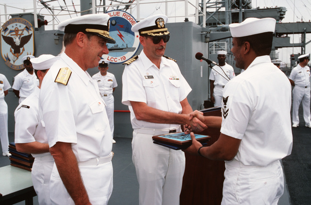 A member of the crew of the US Navy (USN) Amphibious Command Ship USS BLUE RIDGE (LCC 19), receives a re-enlistment plaque from Captain (CAPT) Michael D. Barker, while Vice Admiral (VADM) Henry H. Mauz Jr., commander of the 7th Fleet, looks on.  The fleet is in port for a goodwill visit