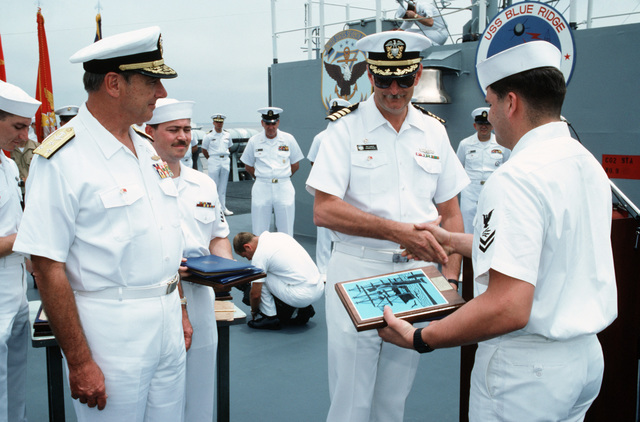 A member of the crew of the US Navy (USN) Amphibious Command Ship USS BLUE RIDGE (LCC 19) receives a re-enlistment plaque from Captain (CAPT) Michael D. Barker, while Vice Admiral (VADM) Henry H. Mauz Jr., commander of the 7th Fleet, looks on.  The fleet is in port for a goodwill visit