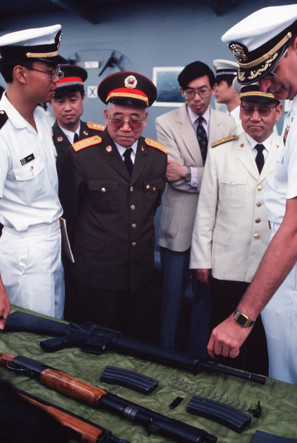 Captain (CAPT) Michael D. Barker, Commanding Officer of the US Navy (USN) Amphibious Command Ship USS BLUE RIDGE (LCC 19), flagship of the 7th Fleet, discusses an American arms display with Chinese military personnel during a four-day goodwill visit in which over 1,600 US Navy Sailors are enjoying the sights and sounds of Shanghai