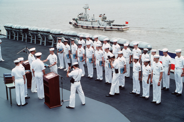 Members of the crew of the US Navy (USN) Amphibious Command Ship USS BLUE RIDGE (LCC 19), flagship of the 7th Fleet, receive re-enlistment plaques from Captain (CAPT) Michael D. Barker, before entering port for a goodwill visit