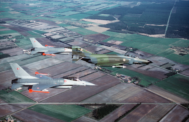 An air-to-air right side view of Danish F-16 Fighting Falcon aircraft from Skydstrup Air Base, Denmark and a 4th Tactical Fighter Wing F-4 Phantom II aircraft from Seymour Johnson Air Force Base, S.C., foreground, en route to a training sortie over northe