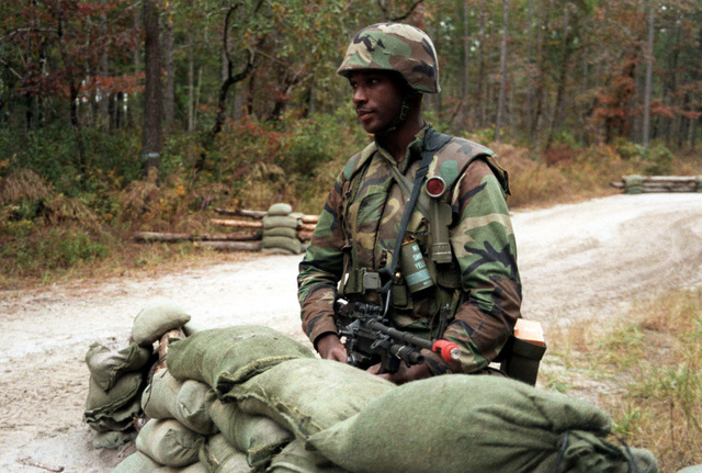 Armed with an M-249 squad automatic weapon (SAW), LCPL Whidbee of Military Police (MP) Co., Headquarters Bn., 2nd Marine Division, stands guard at a checkpoint on an access road leading to the division combat operations center (COC) during the joint services exercise Solid Shield '89