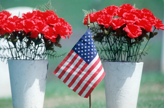 A small American flag and flowers stand at the American cemetery on Memorial Day