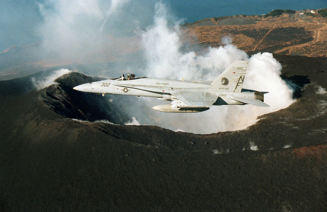 A left side view of an F/A-18A Hornet aircraft from Strike Fighter Squadron 192 (VFA-192) as it passes by Mihara volcano on the island of O-shima off central Japan.  VFA-192, which is part of the air wing assigned to the aircraft carrier USS MIDWAY (CV 41), is based at Naval Air Facility, Atsugi, Japan
