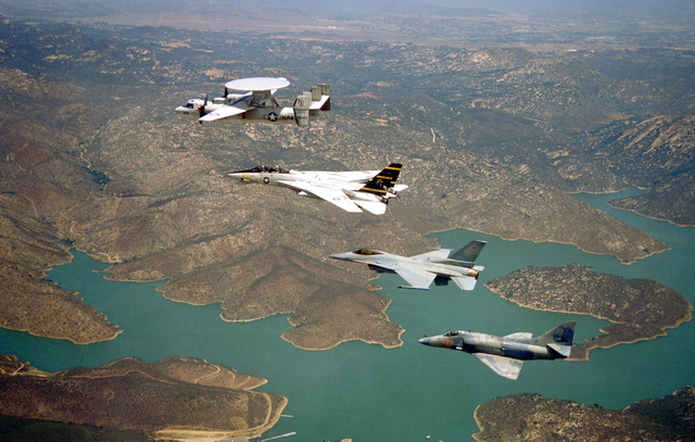 Aerial of an echelon formation led by a US Navy (USN) E-2C Hawkeye, Carrier Airborne Early Warning Squadron 110 (VAW-110), Firebirds, Naval Air Station (NAS) Miramar, California (CA), followed by a USN F-14A Tomcat, Fighter Squadron 124 (VF-124), Gunfighters, NAS Miramar, CA. Two aircraft from Naval Fighter Weapons School (Top Gun), Fighter Squadron 126 (VF-126), Bandits, a USN F-16N Fighting Falcon, and a USN A-4E Skyhawk round out the formation over San Vicente Reservoir
