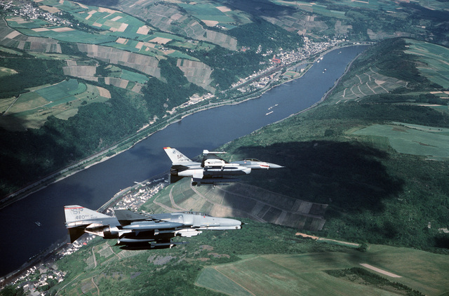 An F-4G Phantom II Wild Weasel aircraft, foreground, and an F-16C Fighting Falcon aircraft fly over the Rhine River. The F-4G, from the 480th Tactical Fighter Squadron, is carrying AGM-88 HARM missiles and AIM-7 Sparrow missiles while the F-16C is armed with an AIM-9 Sidewinder missile and AGM-88 HARM missiles. The F-16C is the aircraft of the 52nd Tactical Fighter Wing commander
