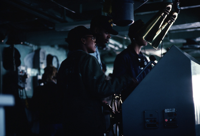 SEAMAN (SN) Smith instructs SN Jules at the helm of the destroyer tender USS YELLOWSTONE (AD 41) as the ship is underway off the Virginia Capes