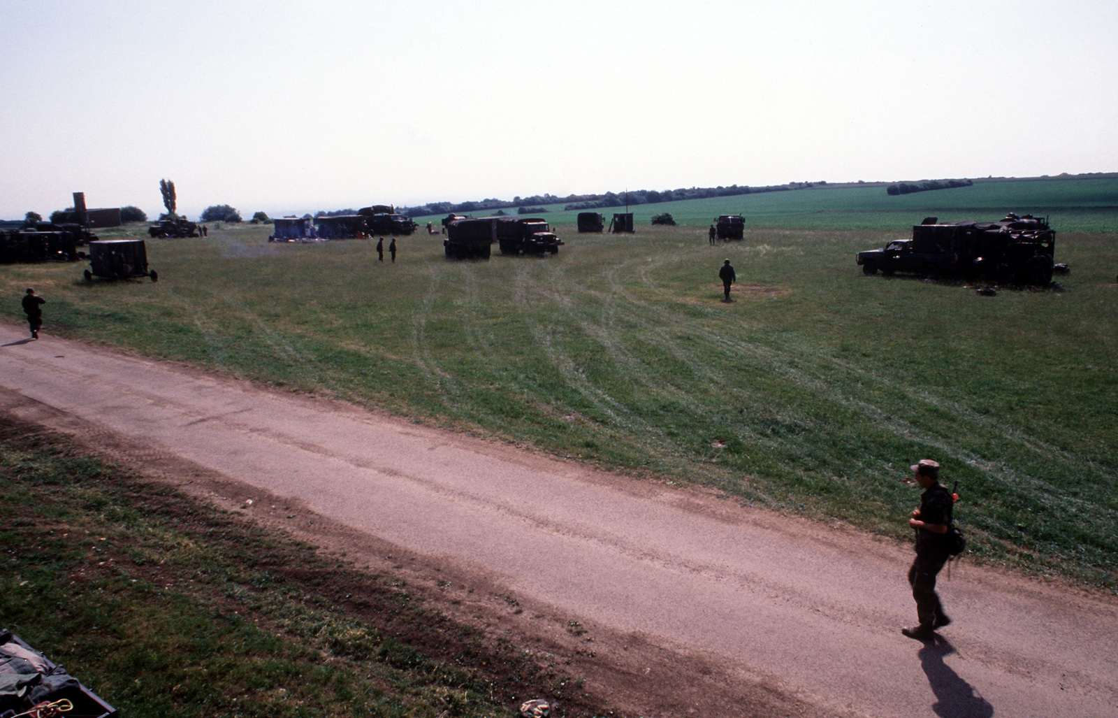 Support vehicles and trailers are dispersed throughout a field in which a mobile radar site will be established during exercise Central Enterprise '89