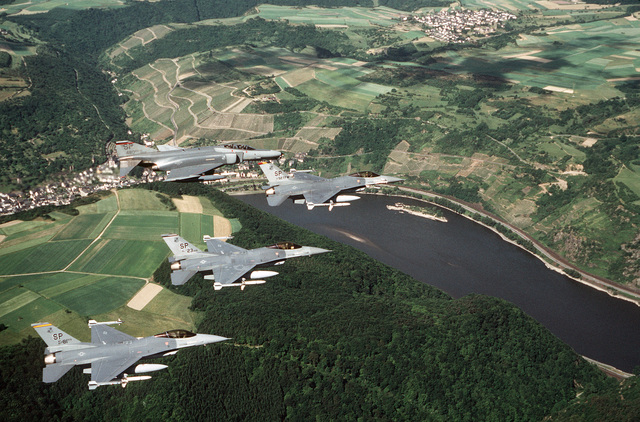Three F-16C Fighting Falcon aircraft and one F-4G Phantom II Wild Weasel aircraft fly over the Rhine River. The Fighting Falcons are armed with AGM-88 HARM missiles and AIM-9 Sidewinder missiles while a HARM missile is visible on the Wild Weasel. The F-16s represent the 81st Tactical Fighter Squadron and the 23rd Aircraft Generation Squadron with the lead aircraft belonging to the commander, 52nd Tactical Fighter Wing. The F-4G is from the 480th Tactical Fighter Squadron