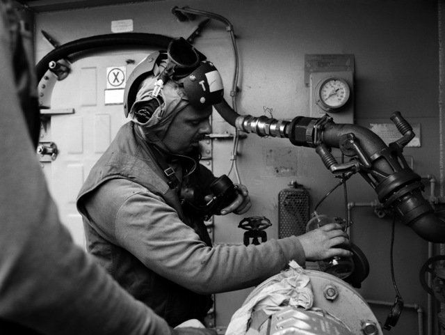 A crewman takes a sample from a fuel station aboard the Guided Missile Cruiser USS JOUETT (CG 29), underway off Southern California