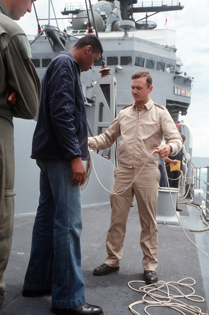 A petty officer explains line handling techniques to a Sailor aboard the Guided Missile Cruiser USS JOUETT (CG 29) off the Southern California coast