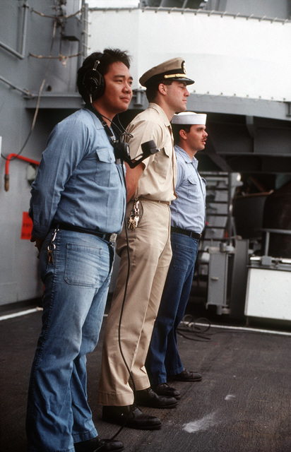 An officer and two Sailors stand at ease on the deck of the Guided Missile Cruiser USS JOUETT (CG 29) off the Southern California coast