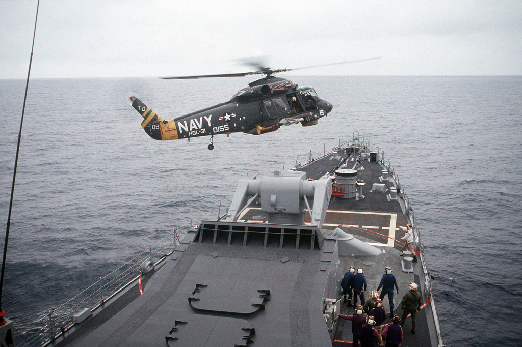An SH-2F Seasprite helicopter of Light Helicopter Anti-submarine Squadron 31 (HSL-31) hovers over the Guided Missile Cruiser USS JOUETT (CG 29) off the Southern California coast, ready to practice removing a man from the deck of the ship