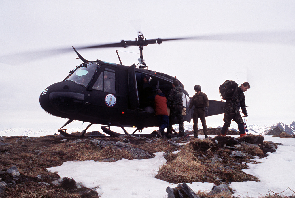 Members of an Air Force recovery team unload their equipment from an Alaska National Guard UH-1 Iroquois helicopter on Barometer Mountain. The team will be clearing the wreckage of an F-15 Eagle aircraft that crashed into the mountain in November 1988