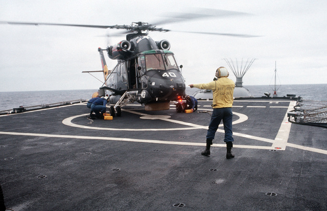 Members of an aircraft handling crew insert chocks against the wheels of an SH-2F Seasprite helicopter aboard the Guided Missile Cruiser USS JOUETT (CG 29) off the Southern California coast, as a plane director signal to the helicopter's pilot