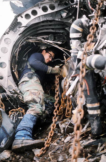 STAFF SGT. Brad Kephart of the 3rd Air Support Operations Center Flight attaches chains to the tail section of a wrecked F-15 Eagle aircraft on Barometer Mountain. A crew of over 40 servicemen is removing unexploded ordnance and other wreckage from the November 1988 crash