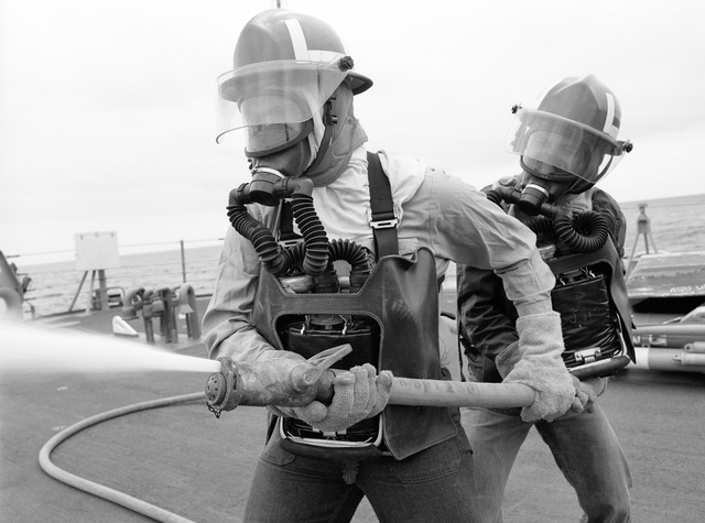 Two firefighters man a hose during a practice session aboard on the Guided Missile Cruiser USS JOUETT (CG 29), underway off Southern California