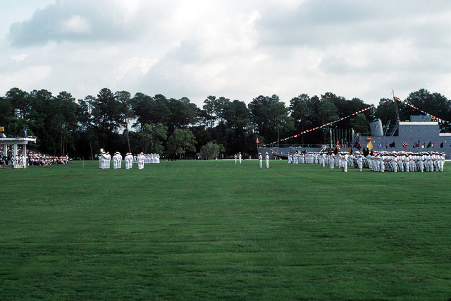 A band plays before the reviewing stand, and recruits stand at parade rest alongside of the training ship mockup BLUE JACKET, during boot camp graduation at the Naval Training Center