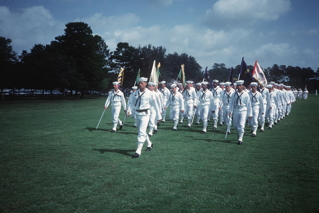 Male recruits pass in review with divisional and other banners during boot camp graduation at the Naval Training Center