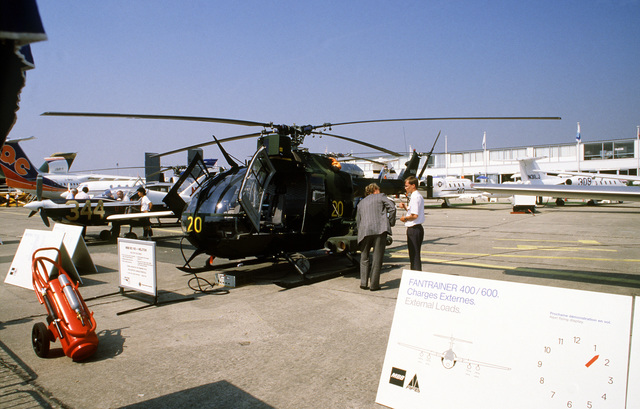 A visitor inspects the tube-launched optically tracked wire-guided (TOW) missile launchers on a West German BO-105 helicopter, near a chart showing external load capabilities for the West German Fantrainer 400/600 series of aircraft. Both aircraft are part of the MBB exhibit at the 38th Paris International Air and Space Show at Le Bourget Airfield