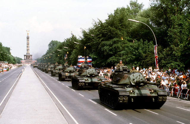 """A column of U.S. Army M-60A1 main battle tanks drives along 17th of June Street during the annual Allied Forces Day parade. The """"Siegessaulte"""" (Victory Column) is in the background"""