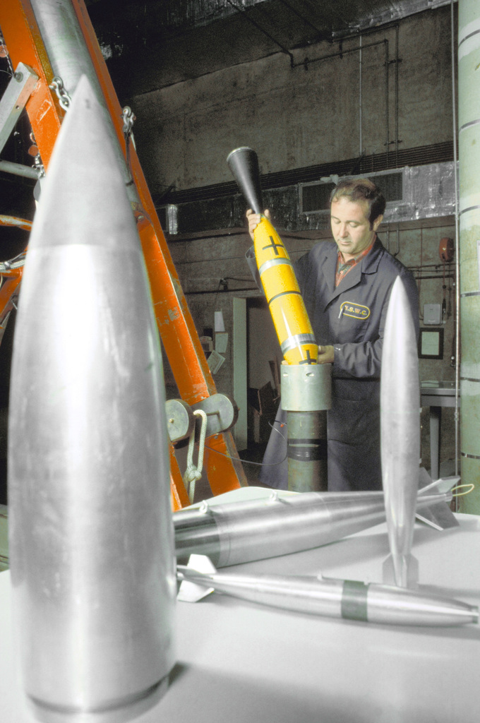 A technician inspects a model prior to its testing in the hypervelocity wind tunnel at the center's high-speed aerodynamics facility