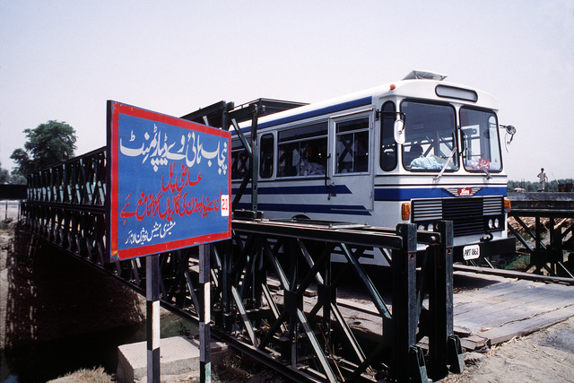 A bus crosses a Bailey Bridge in use on the road between Peshawar and Islamabad. A similar bridge was sent from the U.S. to Pakistan for use by an Afghan guerrilla group that needs to span the Konar River outside of Jalalabad, Afghanistan