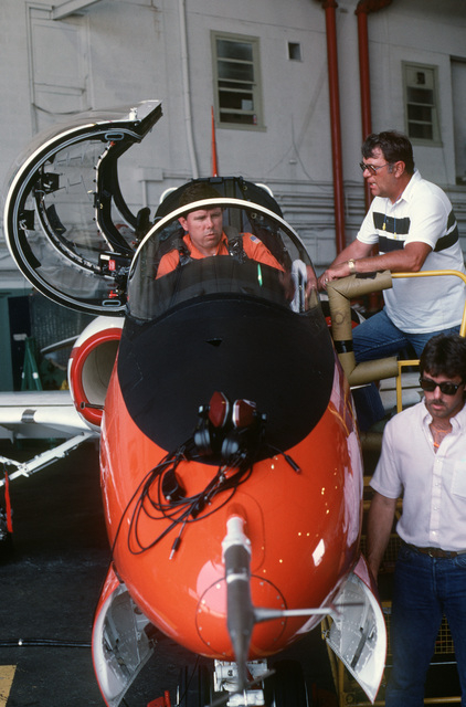 A technician discusses an impending evaluation flight with the pilot of a T-45A Goshawk aircraft.  About 300 Goshawks will be procured by the Navy to replace the T-2C Buckeye and TA-4J Skyhawk trainer aircraft currently in service.  With the capability to land aboard aircraft carriers, The T-45A will be used as an intermediate and advanced student pilot trainer