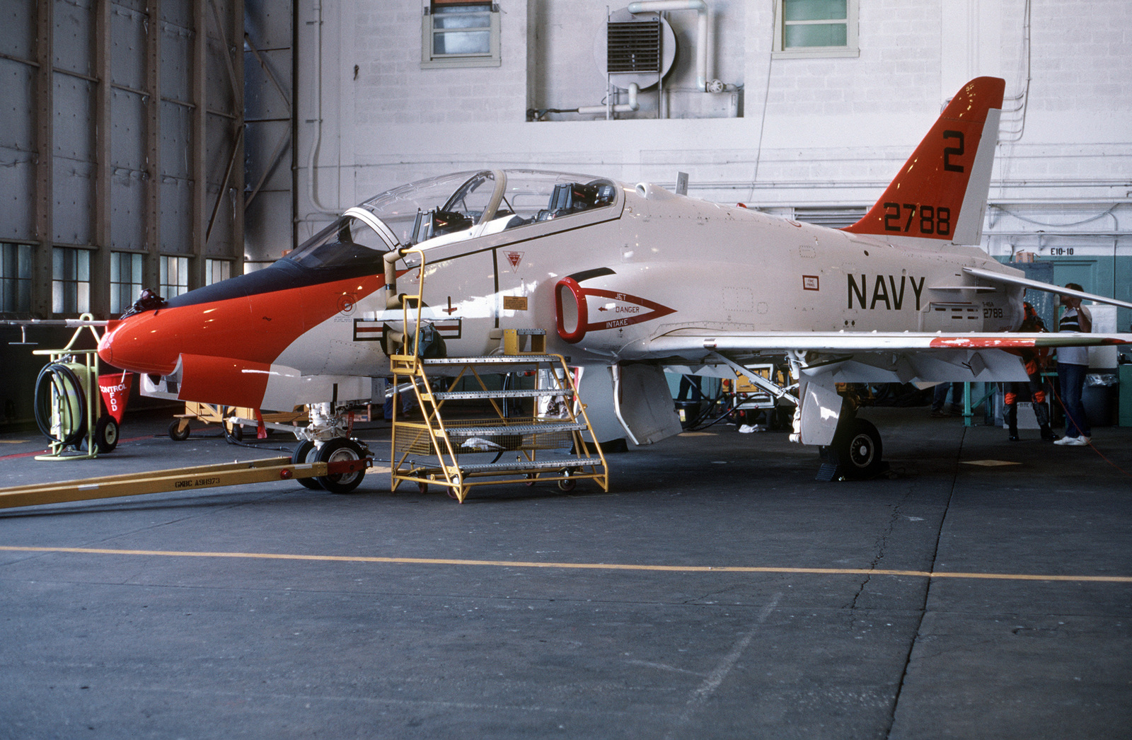 A test pilot checks the tail end of a T-45A Goshawk aircraft prior to an evaluation flight.  The Navy will eventually procure about 300 of these aircraft to replace the T-2C Buckeye and TA-4J Skyhawk trainer aircraft.  The T-45A, which is capable of landing aboard aircraft carriers, will be used for intermediate and advanced student pilot training
