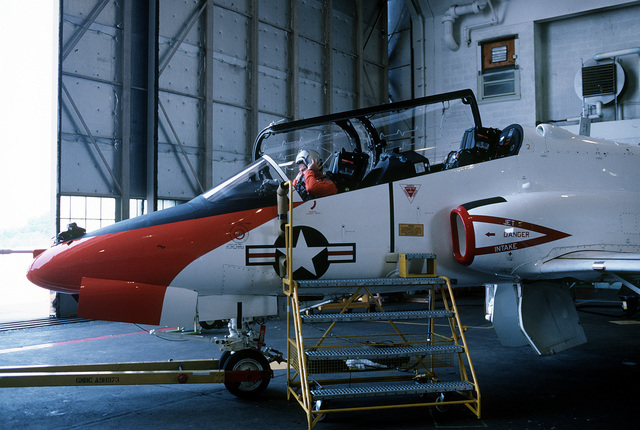 A test pilot dons his helmet before his T-45A Goshawk aircraft is towed from a hangar onto the flight line. The Navy will eventually procure about 300 T-45As, which are able to land aboard aircraft carriers. The Goshawk will replace the T-2C Buckeye and TA-4J Skyhawk aircraft for intermediate and advanced student pilot training