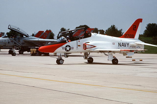 A test pilot taxis a T-45A Goshawk aircraft past a row of F-14A Tomcat aircraft. The Navy is evaluating the aircraft, which is an intermediate and advanced student trainer capable of landing aboard aircraft carriers. About 300 T-45As will be procured to replace the T-2C Buckeye and TA-4J Skyhawk trainer aircraft currently in service