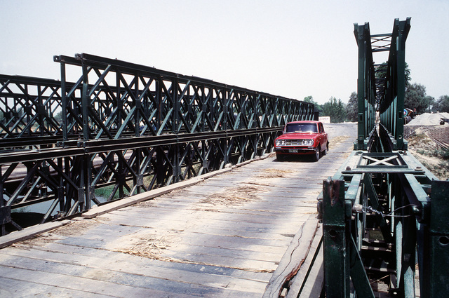An automobile crosses a Bailey Bridge in use on the road between Peshawar and Islamabad. A similar bridge was sent from the U.S. to Pakistan for use by an Afghan guerrilla group that needs to span the Konar River outside of Jalalabad, Afghanistan