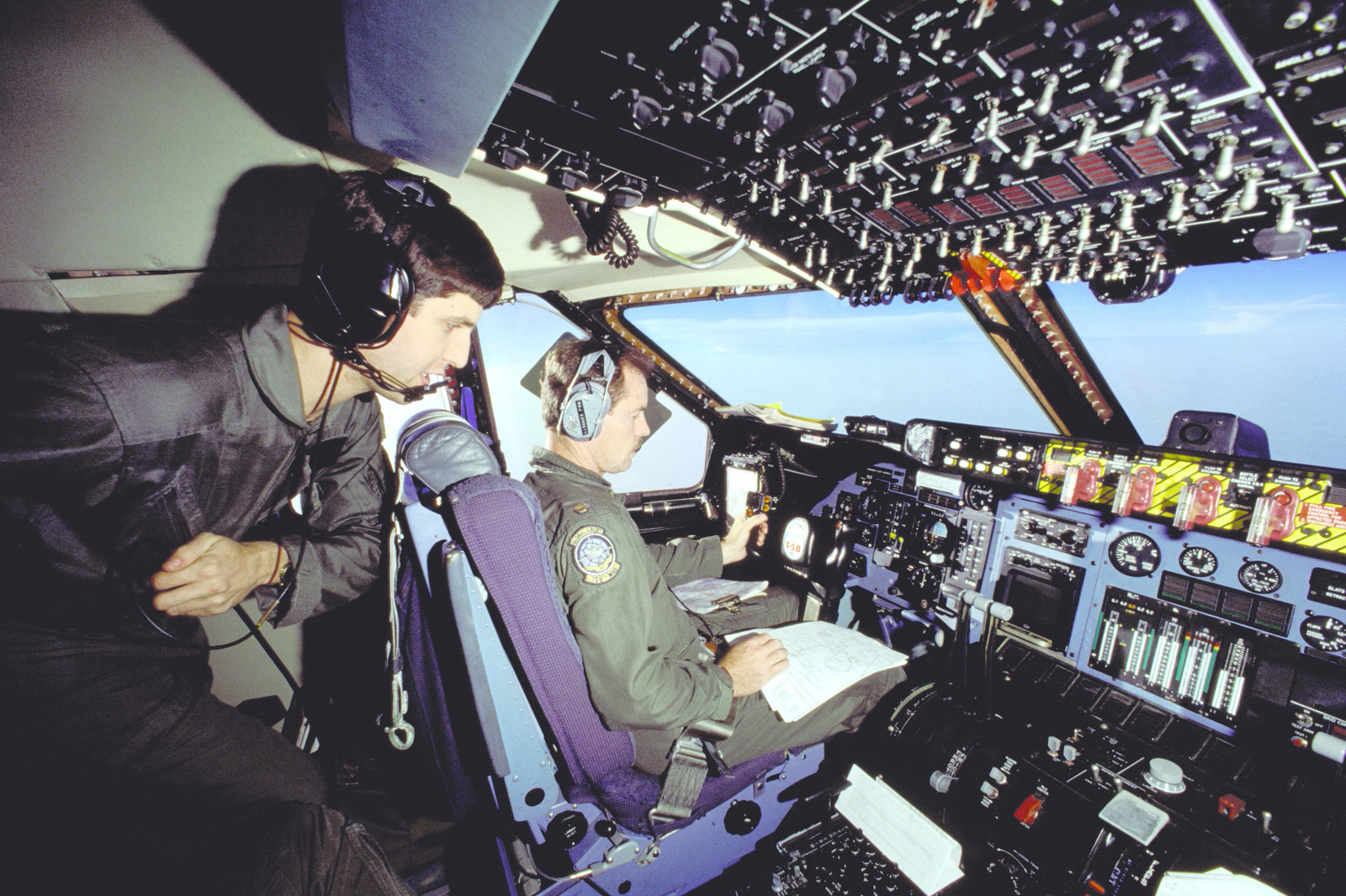 In the cockpit of a 709th Military Airlift Squadron (709th MAS) C-5B Galaxy aircraft, Thomas Van Hare of the Office of the Secretary of Defense, Humanitarian Assistance Office, discusses landing support requirements with MAJ Charles Corbet, the pilot of one of two 709th MAS aircraft that are delivering a Bailey Bridge to Islamabad, Pakistanm. The portable bridge will be passed on to an Afghan guerilla group that will use it to span the Konar River outside of Jalalabad, Afghanistan