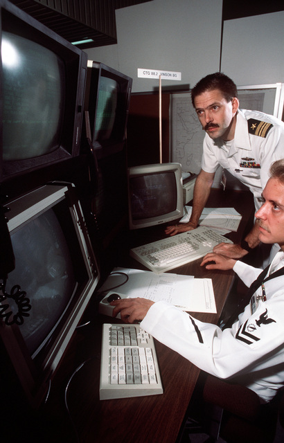 Lieutenant Commander (LCDR) Mike Harrel, standing, watches as Data Processing Techinician Second Class (DP2) Craig Corder uses the Enanced Naval Warfare Gaming System (ENWAGS) at the Naval War College