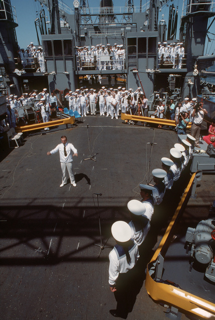 "American naval personnel salute as a group of Soviet vocalists perform""The Star Spangled Banner""during a performance aboard the Replenishment Oiler USS MILWAUKEE (AOR 2).  For the first time, Soviet naval vessels are visiting an American port.  The Guided Missile Cruiser MARSHAL USTINOV (CG 088), the Guided Missile Destroyer OTLICHNYY (DDG 434) and the Replenishment Oiler GENRIKH GASANOV are in Norfolk for a five-day goodwill visit"