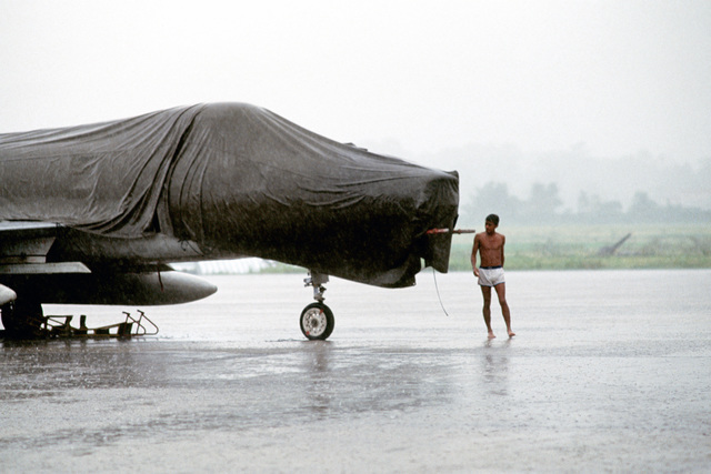 A Honduran air force technician wearing a bathing suit secures a cover over a Super Mystere B.2 aircraft in a driving rainstorm at Goloson Airport during Exercise AMIGO SOUTH.  Thirty members of the US Air Force's 425th Tactical Fighter Training Squadron