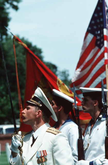 A Soviet officer leads a guard for the Soviet and American colors during ceremonies for US World War II dead, at Hampton National Cemetery.  The Slava Class Guided Missile Cruiser MARSHAL USTINOV (CG 088), the Sovremenny Class Guided Missile Destroyer OTLICHNYY (DDG 434) and the Oiler GENRIKH GASANOV are making the first-ever Soviet naval visit to a US military port