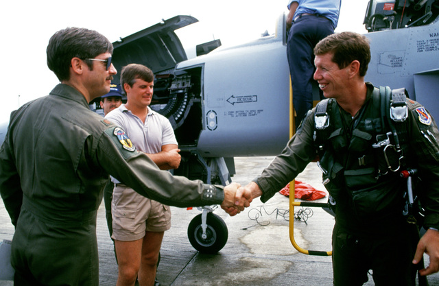 Two pilots from the 425th Tactical Fighter Training Squadron (425th TFTS) shake hands after the arrival of the pilot at right.  Behind them, civilian technicans work on an F-5E Tiger II aircraft. Thirty members of the 425th TFTS are in Honduras to support