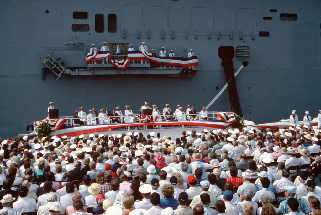 A large crowd listens to a speech as crewmen man the rails during the commissioning ceremony of the Amphibious Assault Ship USS WASP (LHD 1).  The first ship in its class, WASP combines flight deck and well deck capabilities with a state-of-the-art combat information center and several newly developed systems